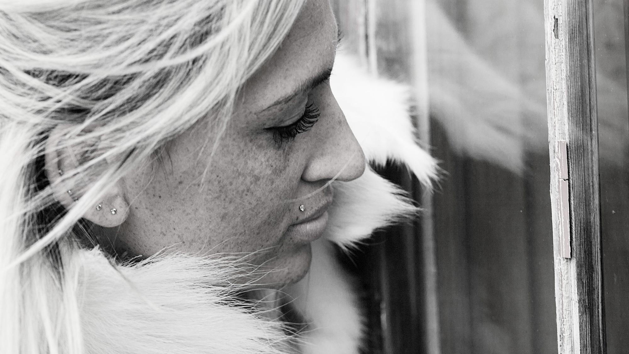 Junge Frau blickt verträumt durch ein Fenster ins Innere einer Hütte.